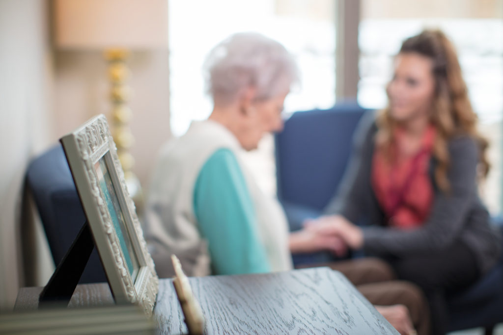 A mother and daughter having a conversation with a picture frame in view.