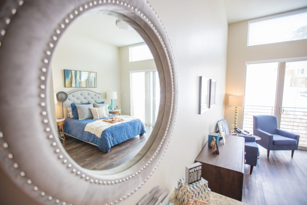 A luxurious bedroom reflected in a mirror on the wall.