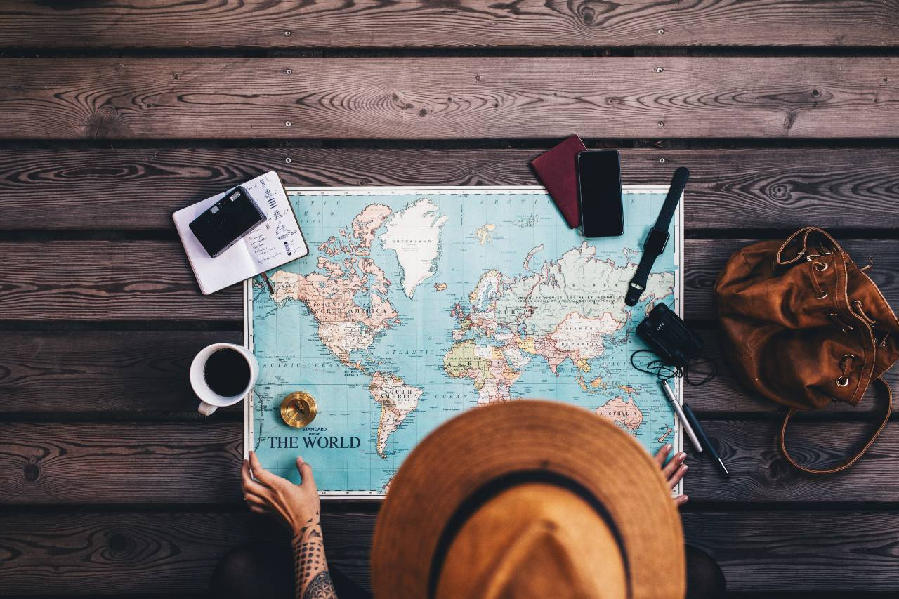 A woman looks at a world map and makes travel plans