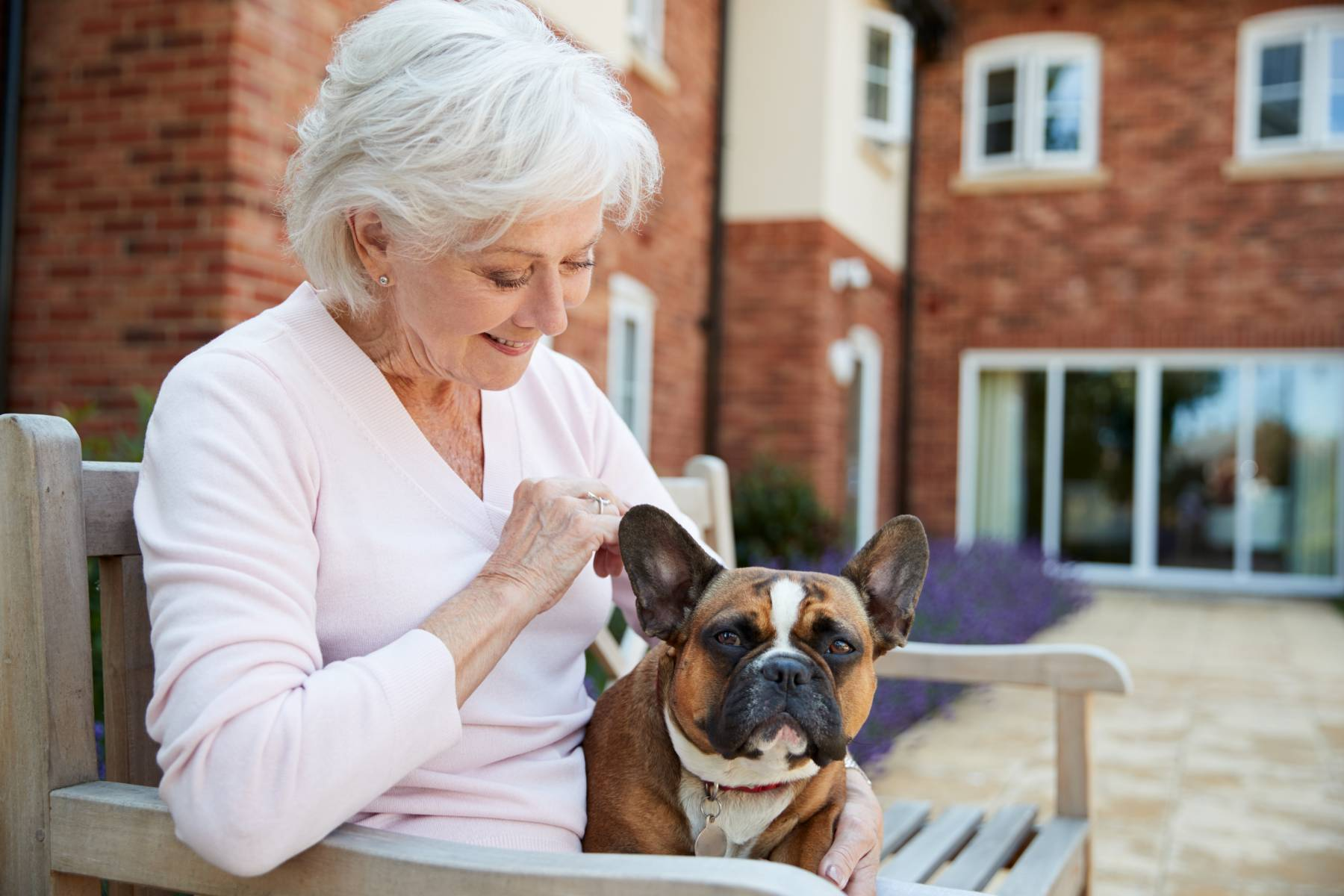 senior woman petting her dog while sitting outside on a bench