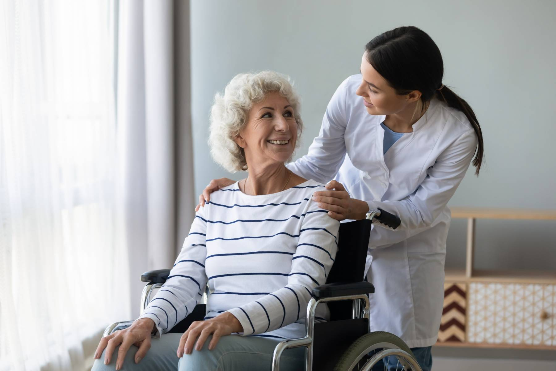 senior lady in assisted living while talking with a healthcare worker