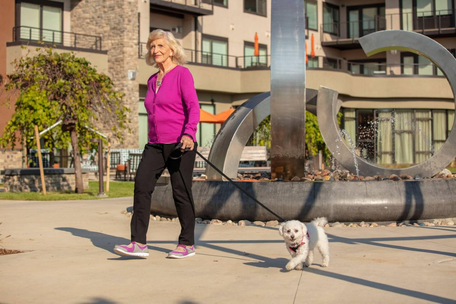 senior woman walking her dog at The Ridge Pinehurst