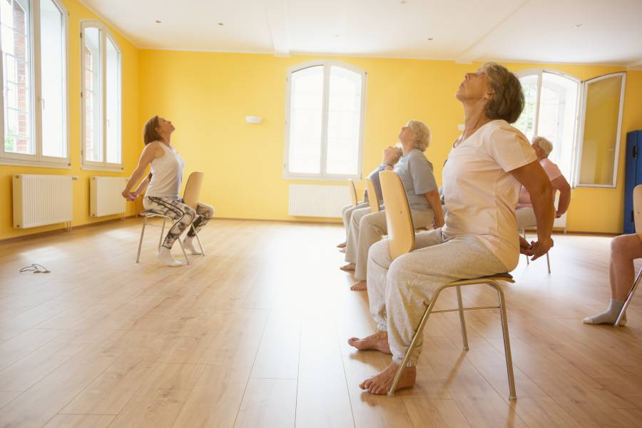 A group of seniors take a chair yoga class
