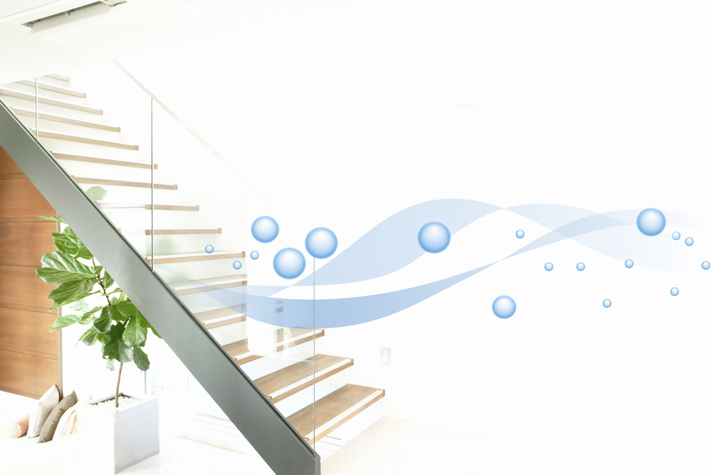 example of an air purification, with blue waves and bubbles implying clean air floating through a living space with a plant and couch and stairs in the background