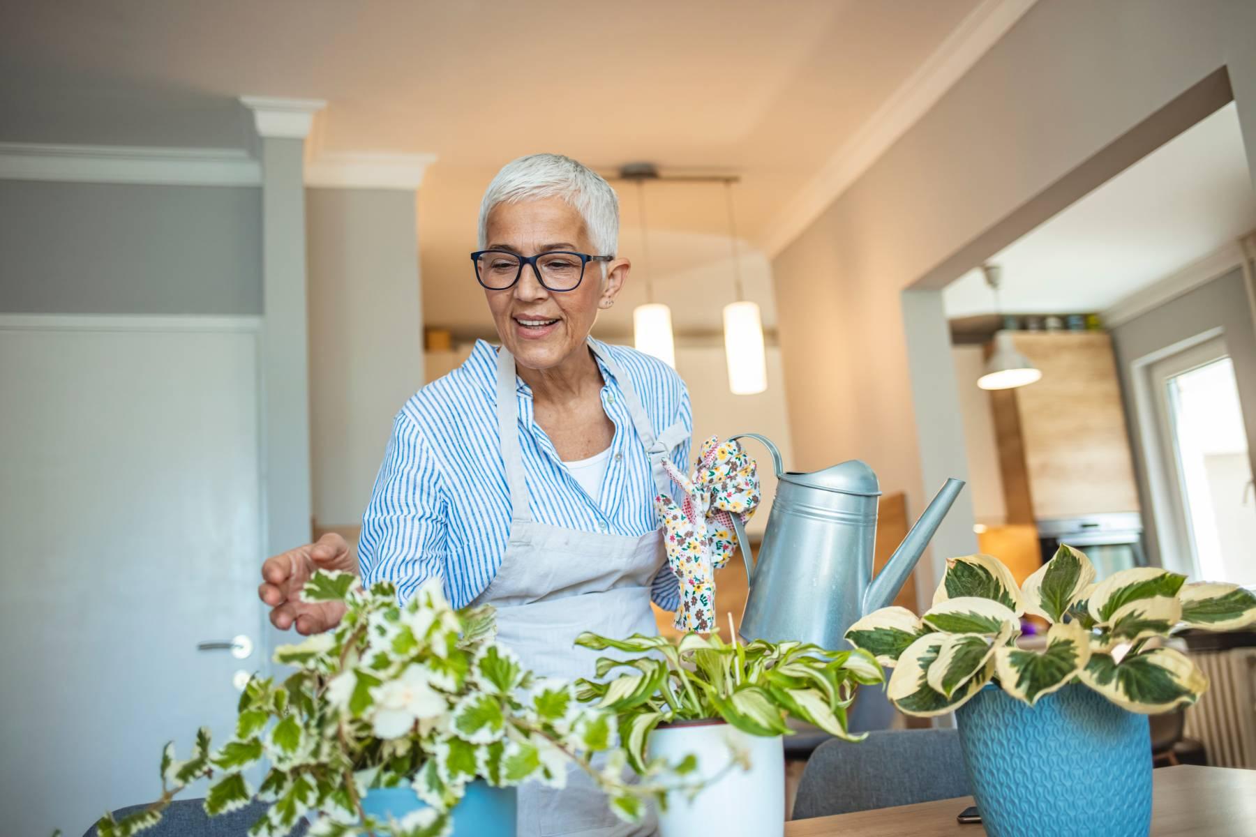 senior woman watering indoor plants in a senior apartment
