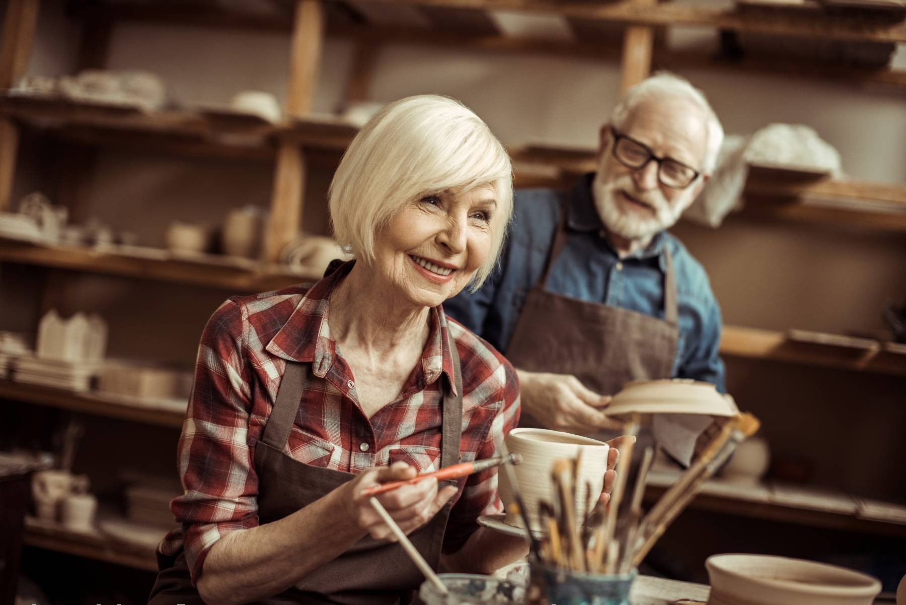 senior couple making pottery together at an art class
