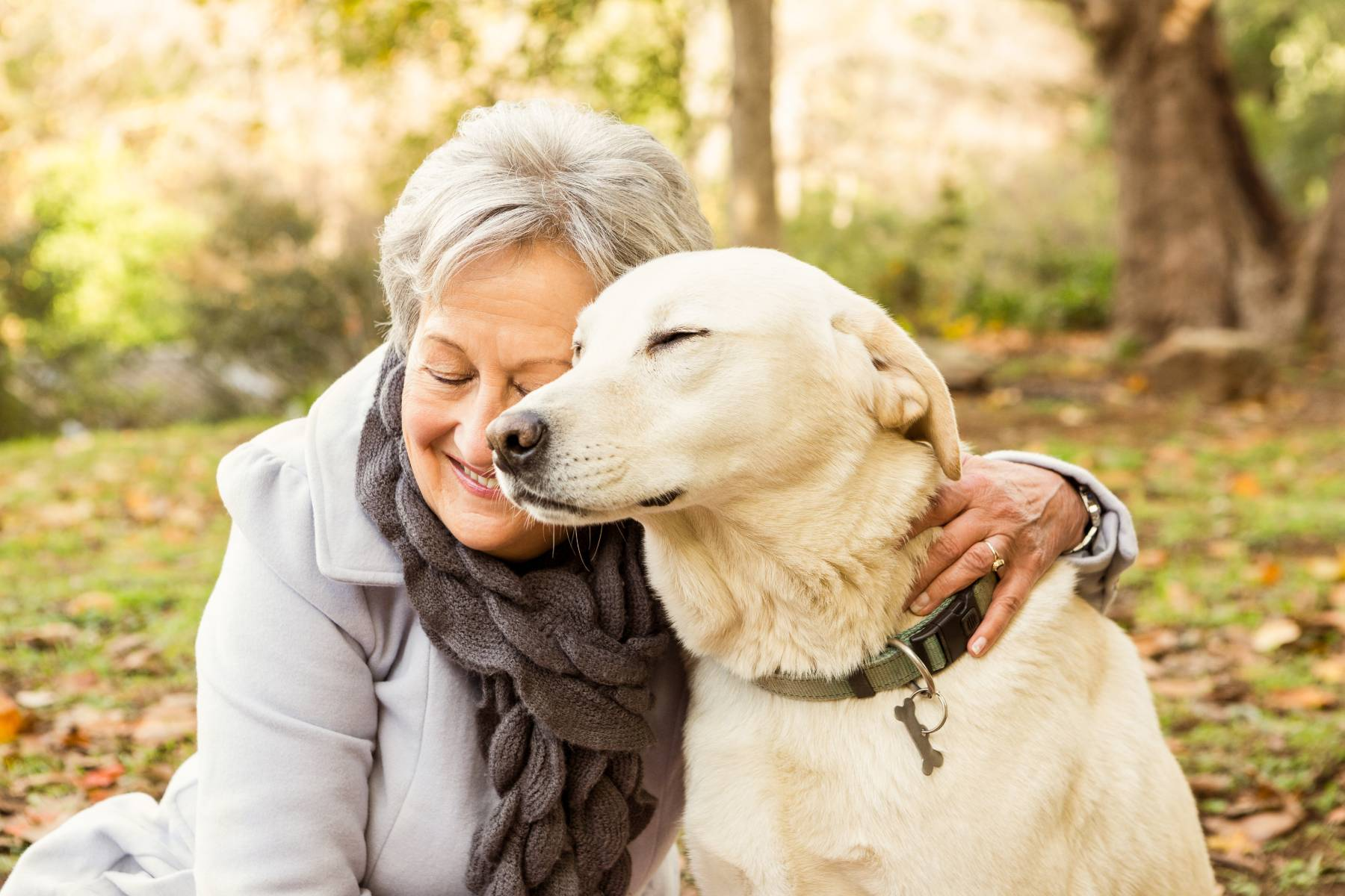 senior woman snuggling with her dog outside