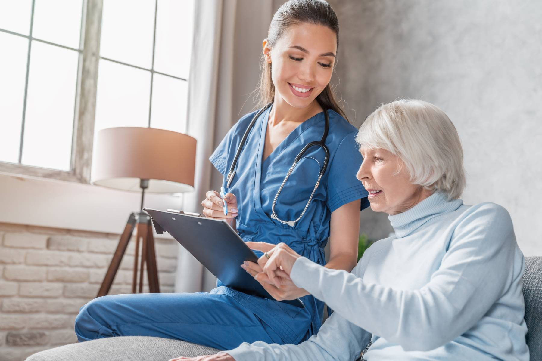 senior lady talking with a nurse while looking over a health chart