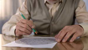An elderly man uses a pencil to work on a maze puzzle