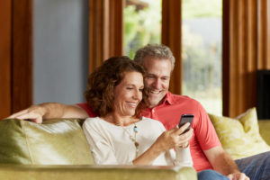 A senior couple sit on a couch and look at a iPhone