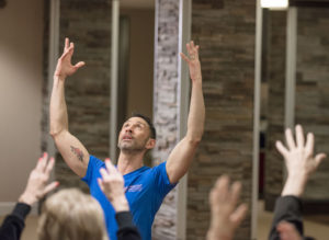 A fitness instructor leads a class of seniors in exercise movements