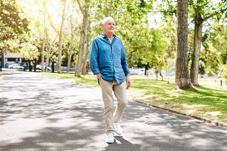 A senior man walks on a tree lined path in summer
