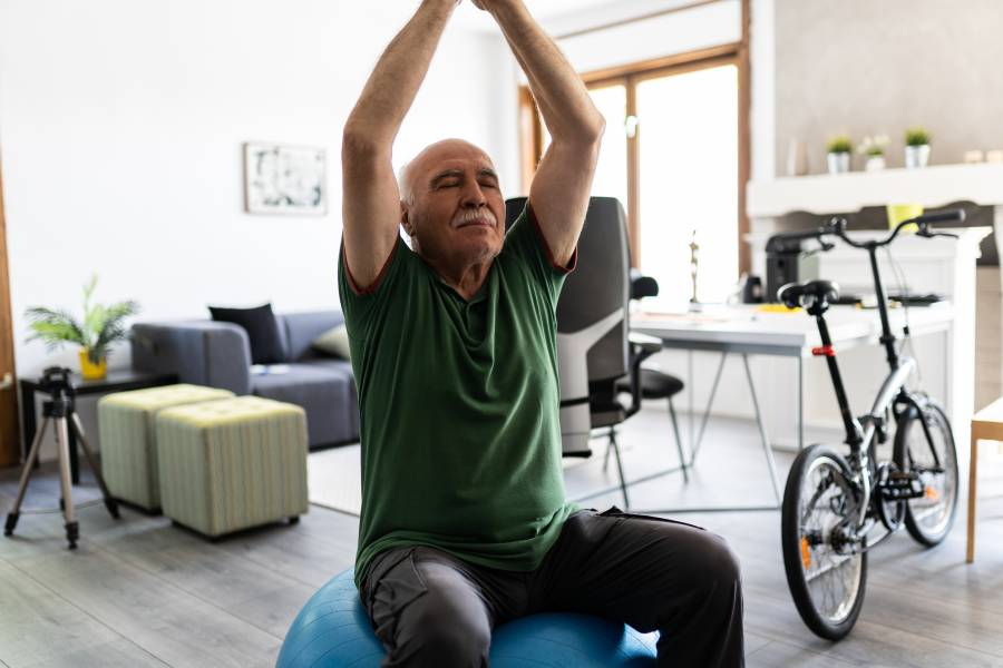 A senior man sits on a balance ball and stretches his arms above his head