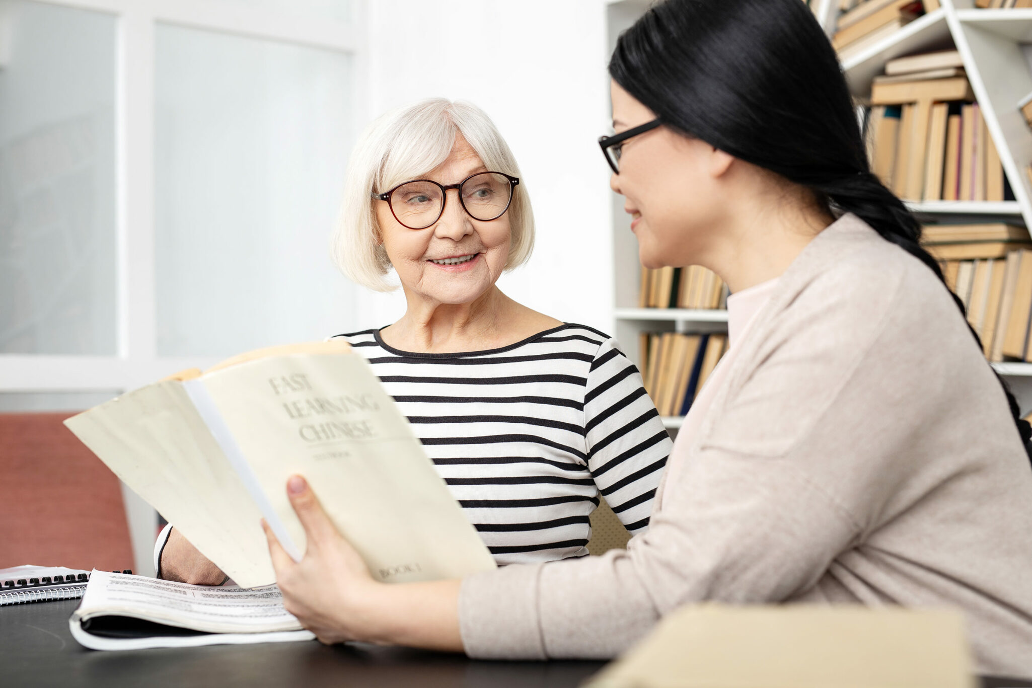 A woman helps a senior woman study from a book