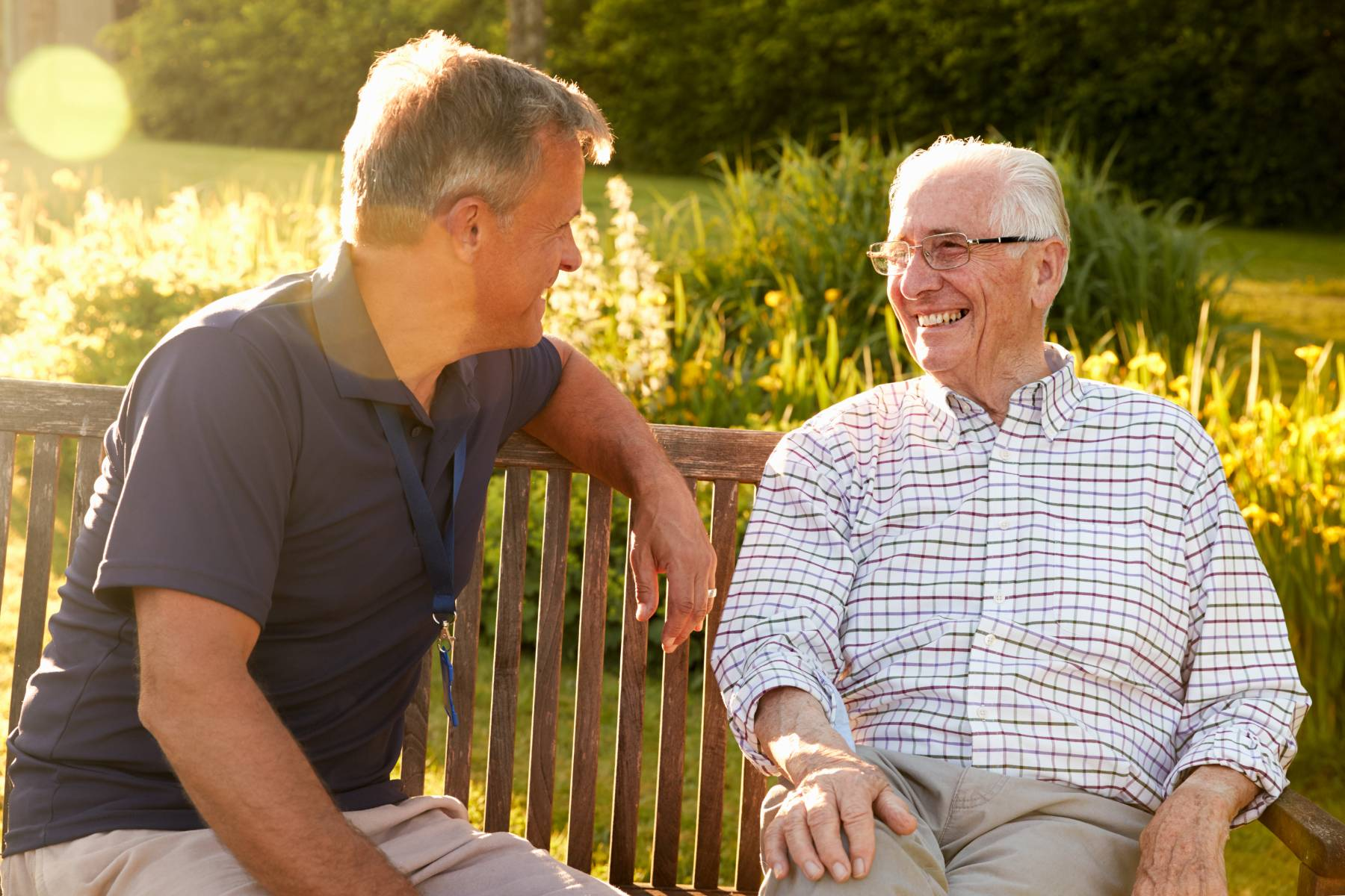 two men talking with one another outside on a bench