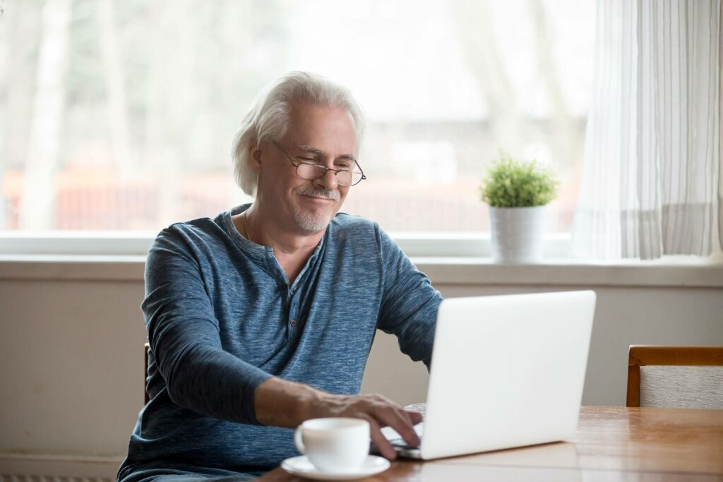 A senior man drinks coffee while looking at his laptop