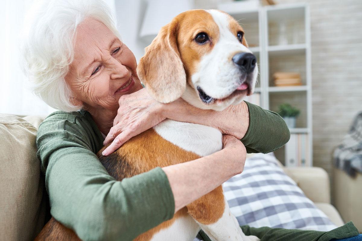An elderly woman hugs her hound dong