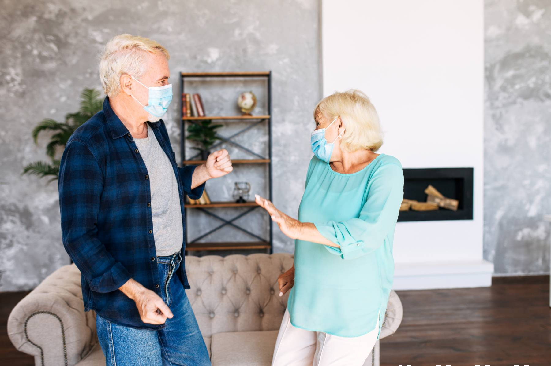 seniors wearing masks dancing in the living room of a senior apartment