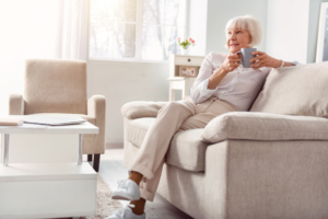 A senior woman sits on a couch and enjoys a cup of coffee