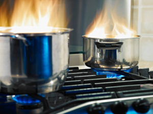 Two silver pots on a stove with steam rising up