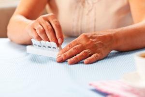A closeup of a senior woman placing medication into a weekly pill sorter.