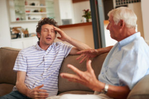 A photo of a senior man and his father having an argument