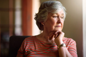 Shot of a thoughtful senior woman looking out of the window at home