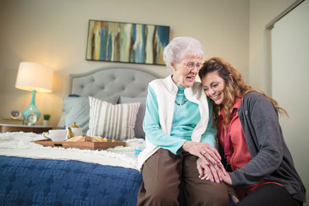 A health care professional hugs an elderly woman who lives in assisted living