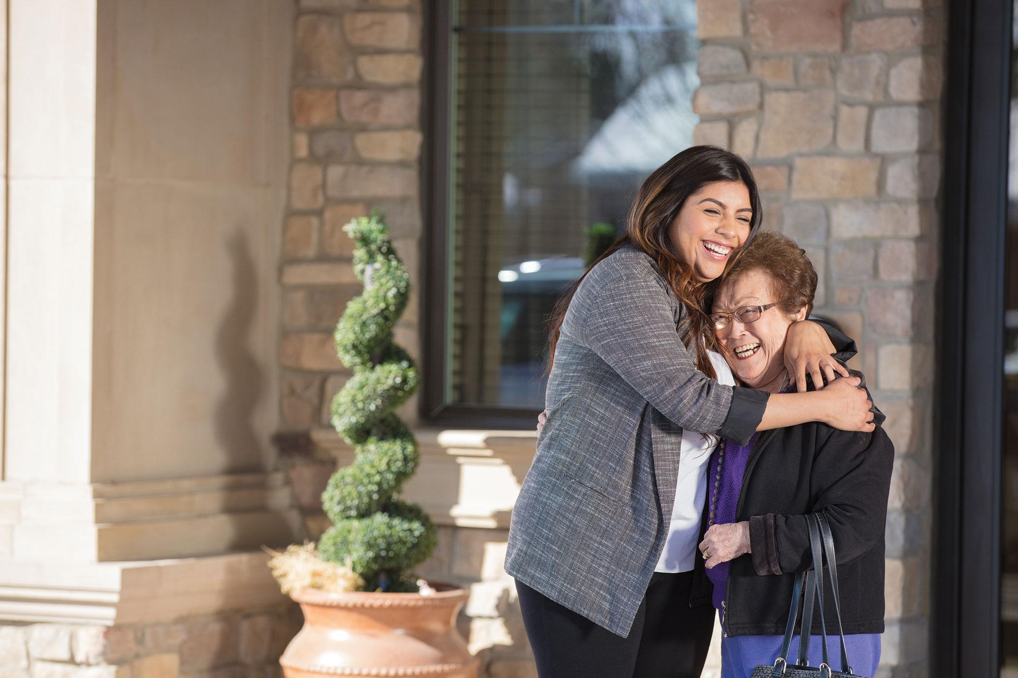A senior living staff member hugs a senior woman