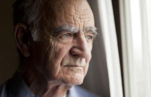 Elderly man looking out a window