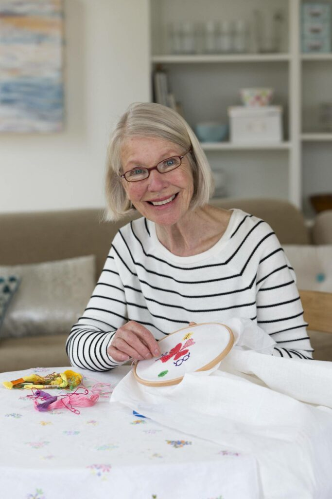 A senior woman works on a cross stitch project