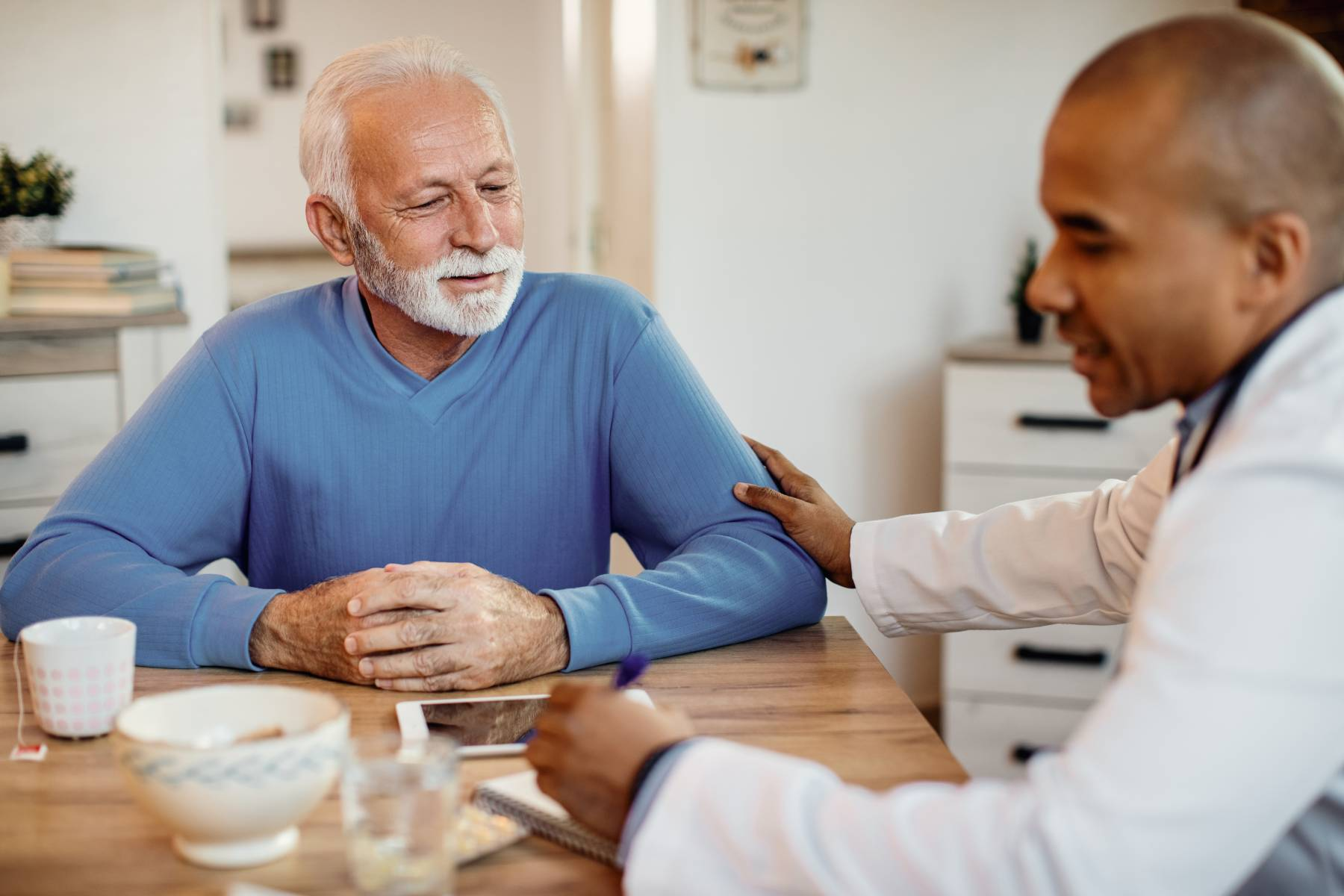 senior getting help with medication management with a health care worker in assisted living