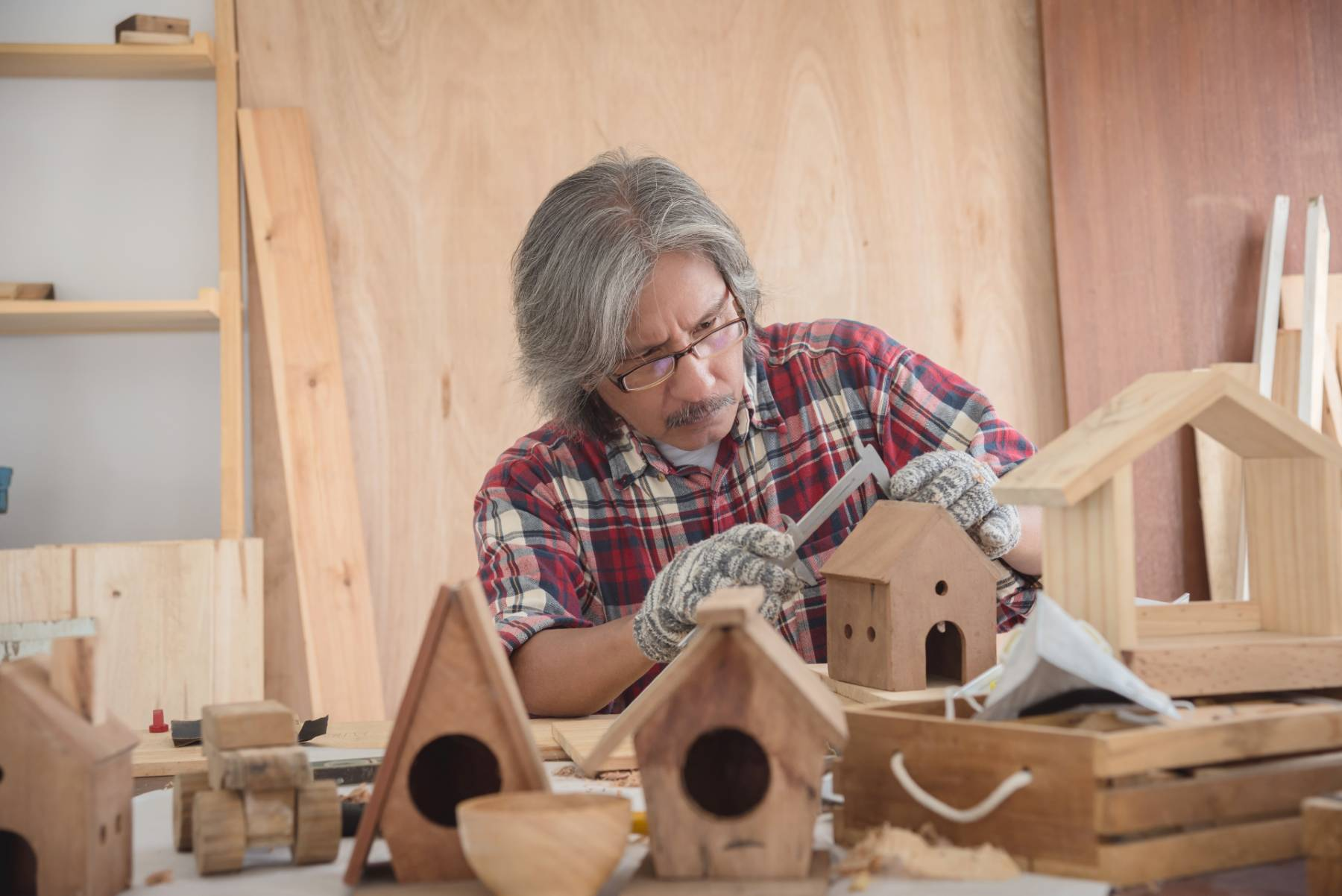 A senior man works on Christmas woodworking projects