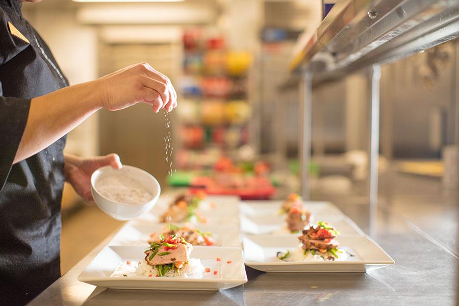 Chef sprinkling salt on top of meals