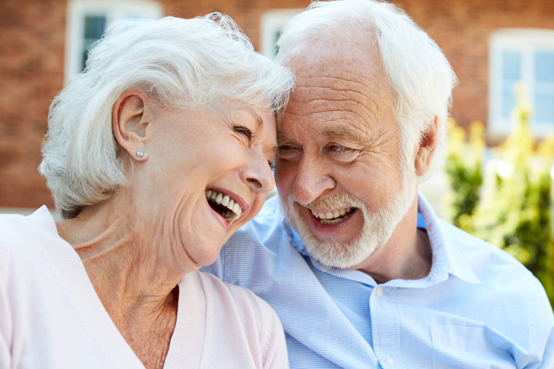 senior couple in assisted living smiling and laughing outside