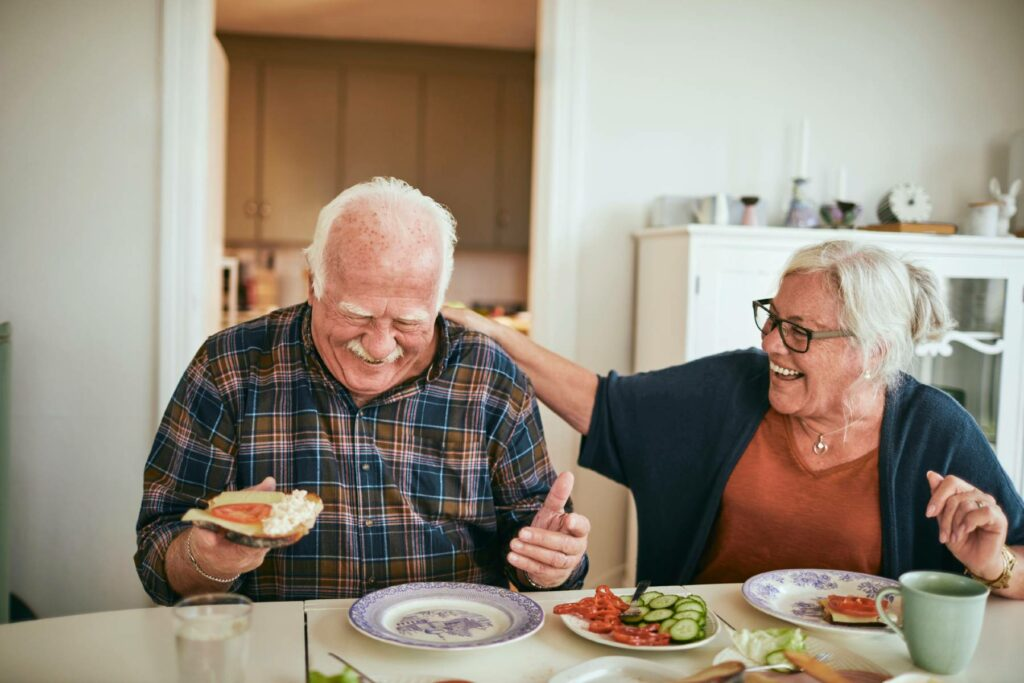 A senior couple laugh while eating brunch at home together