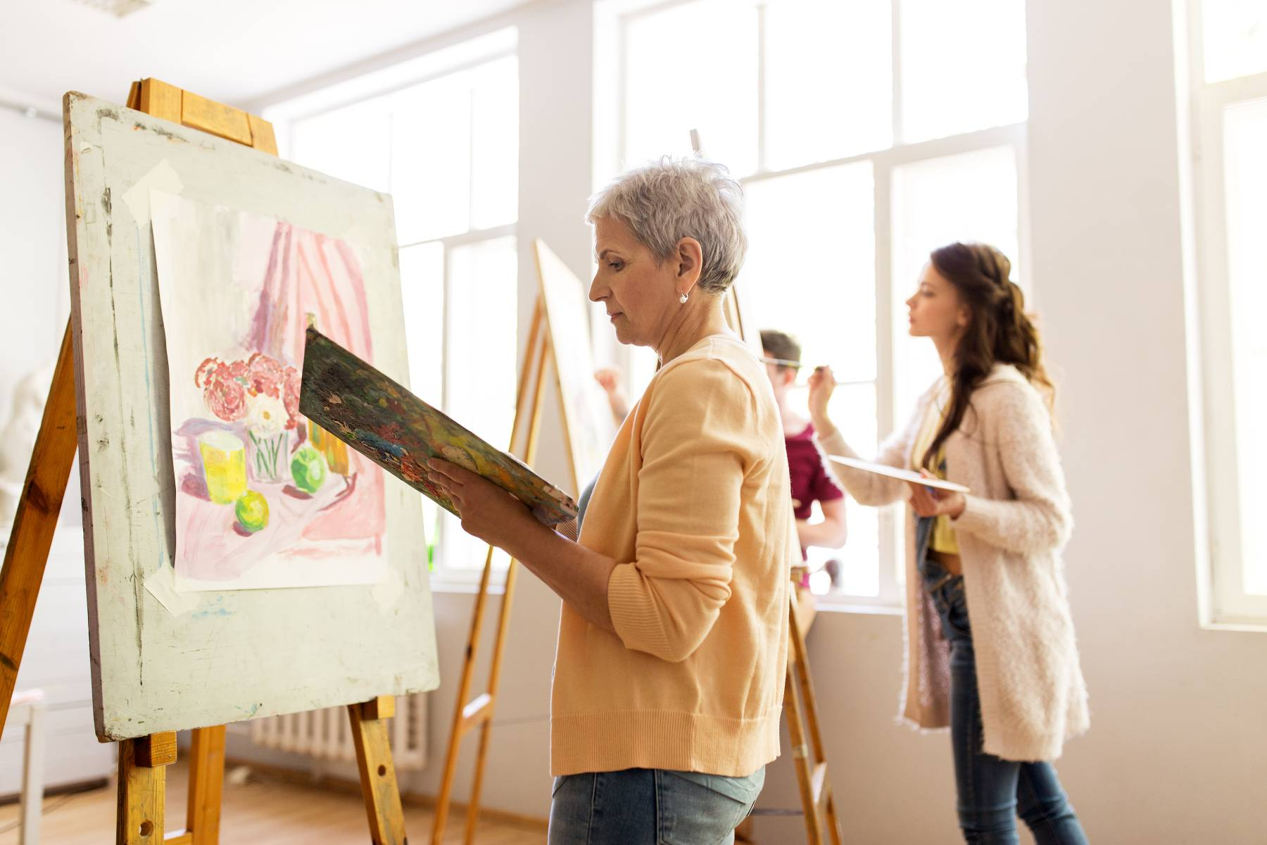 seniors painting in an art class at a senior living community