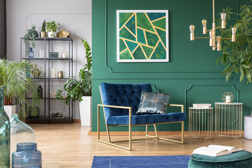 An apartment with a teal green wall and modern feel with lots of indoor plants