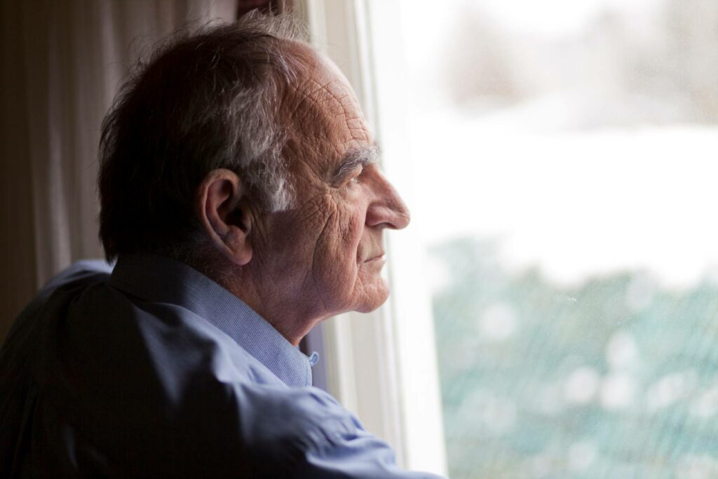 An elderly man is deep in thought while looking out a window