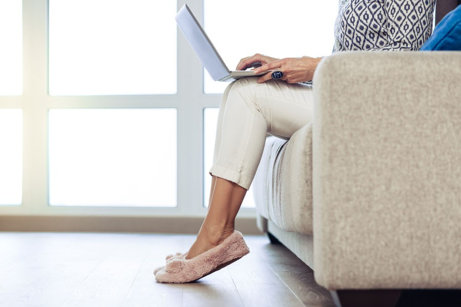 A woman sits on a couch and looks at her laptop