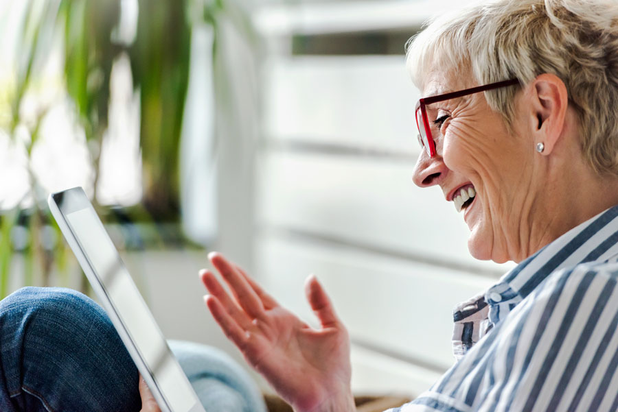 A woman laughs and smiles while looking at her tablet