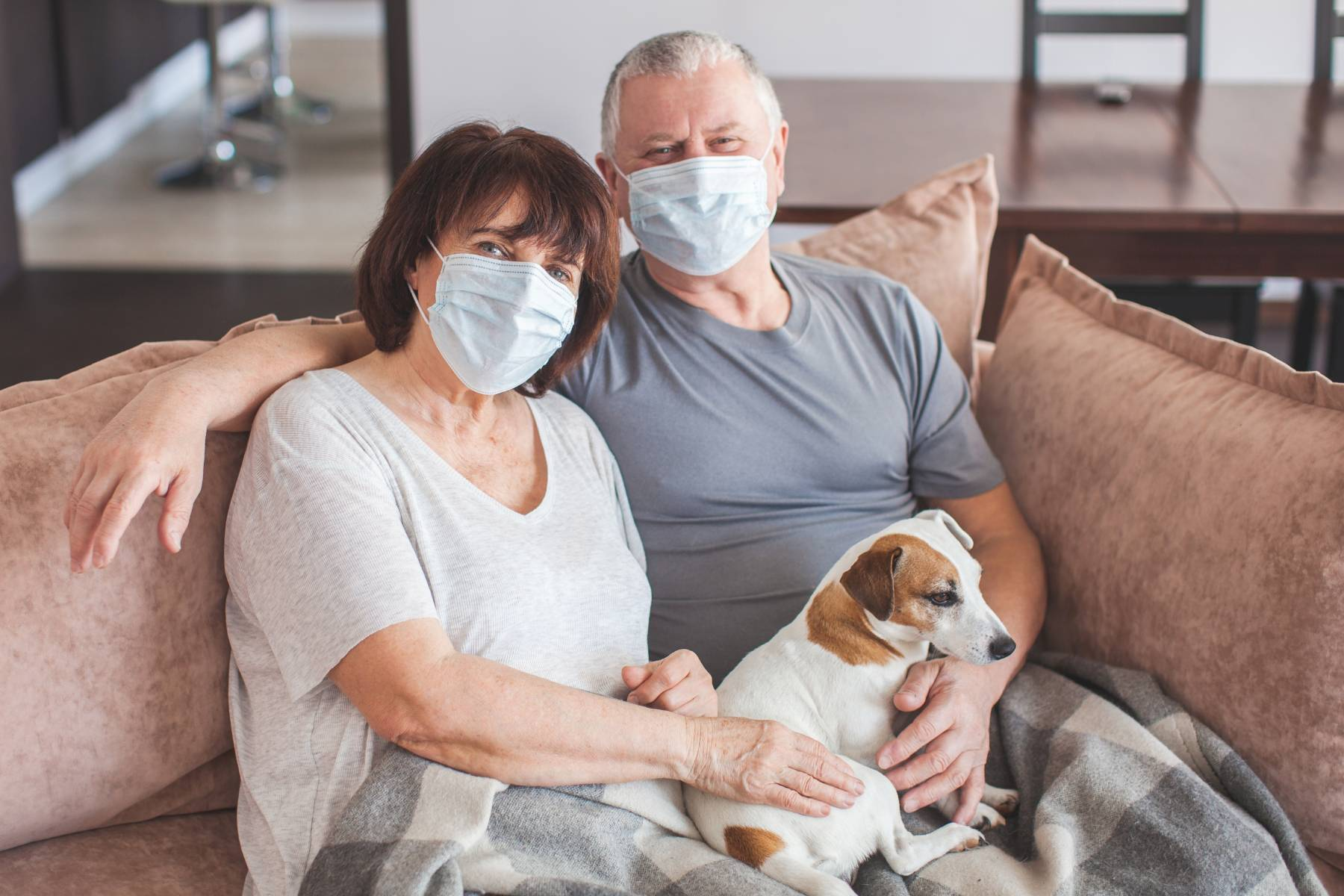 senior couple sitting on a couch with their dog