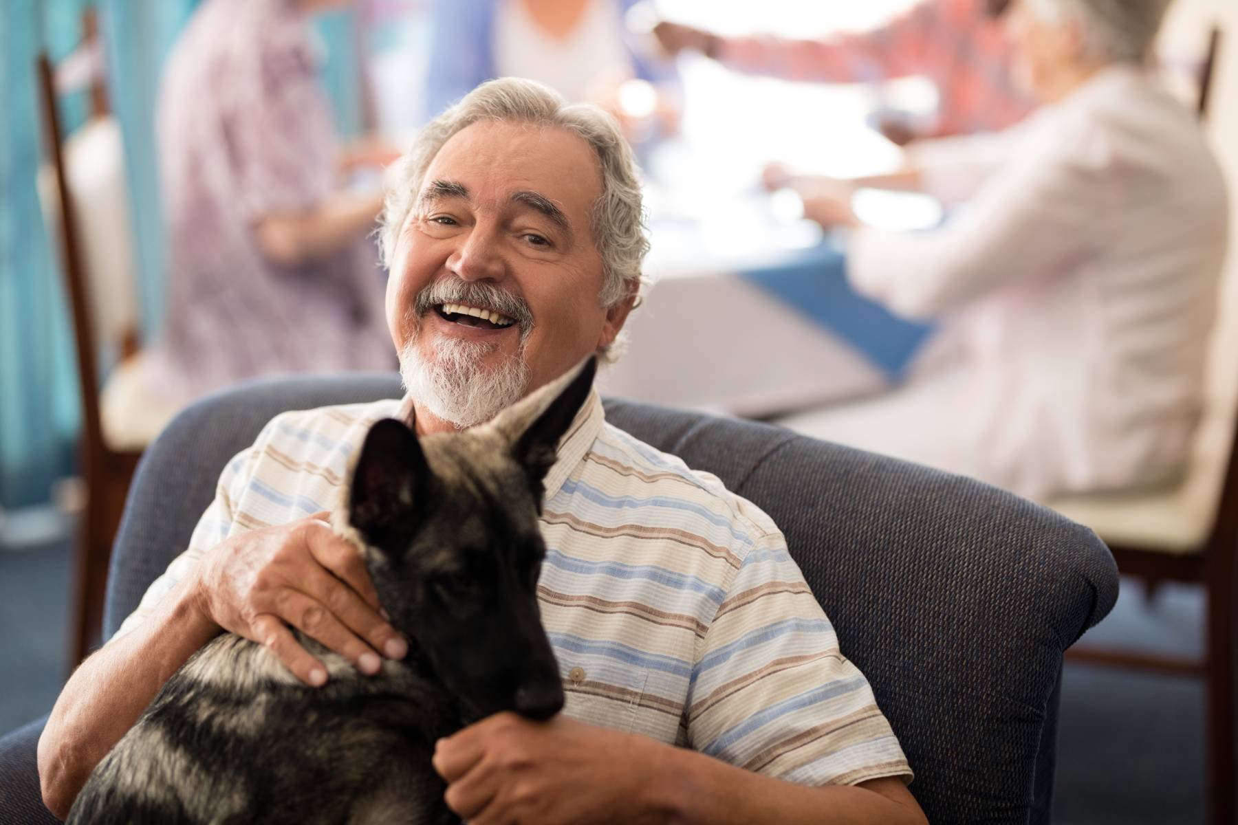 senior man sitting with his dog in a pet friendly assisted living community