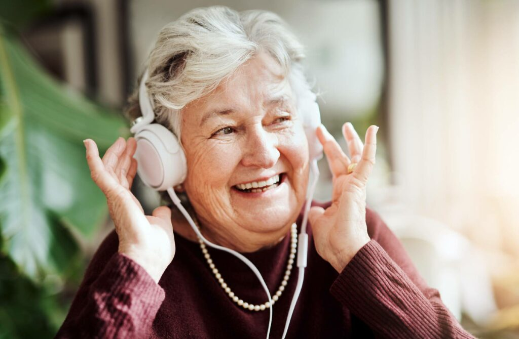 A senior woman smiles while listing to over the ear headphones