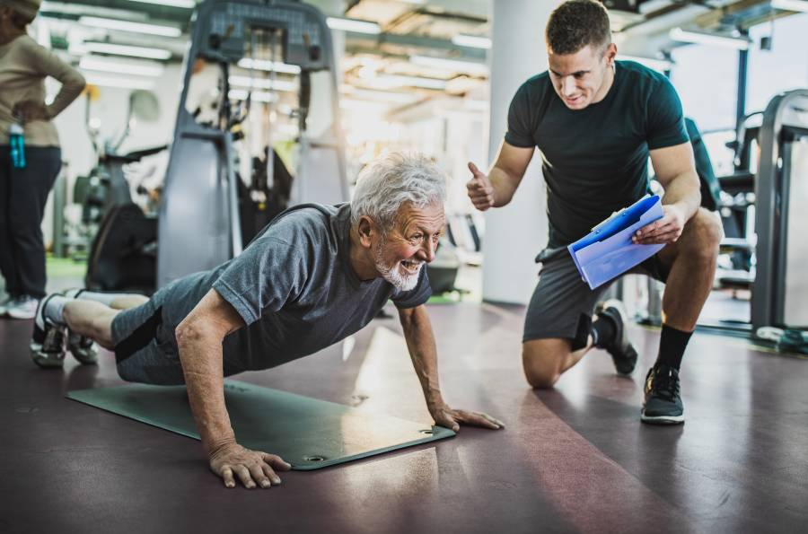 A trainer cheers on a senior man doing push ups in the gym