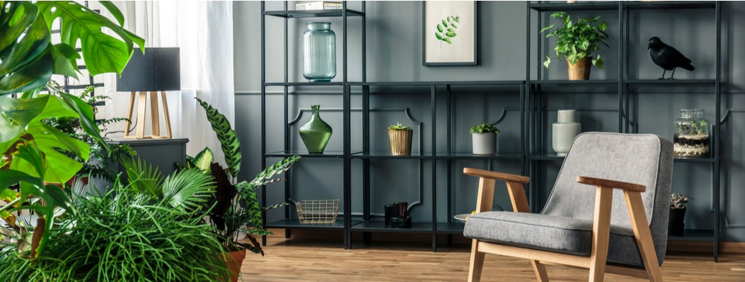 A modern apartment with dark walls and metal furniture and lots of indoor plants