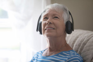 A senior woman listens to music with over the ear headphones