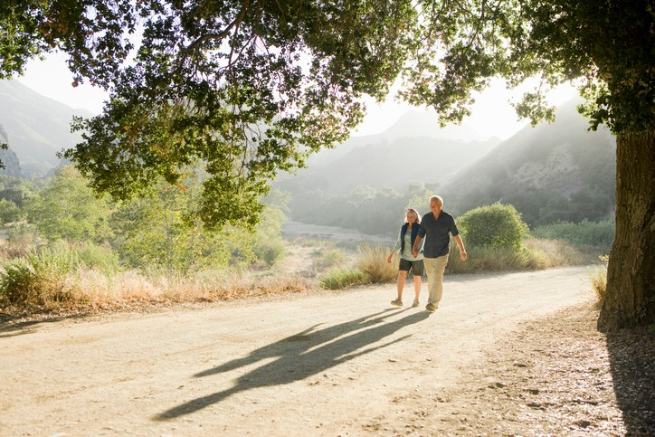 A couple go for a walk outside on a rural countryside trail