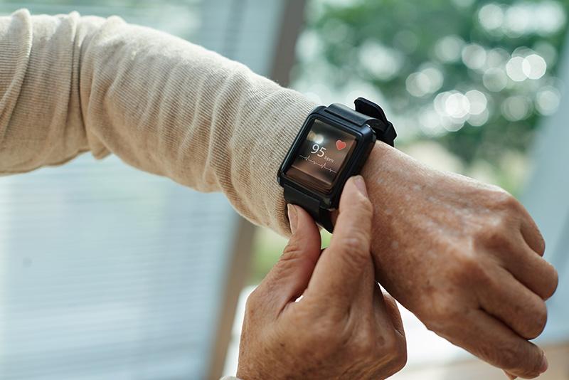 A senior citizen using a heart monitoring watch.