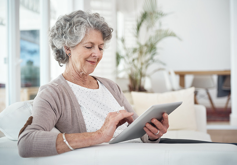An elderly woman sitting in a sunny room using a tablet.
